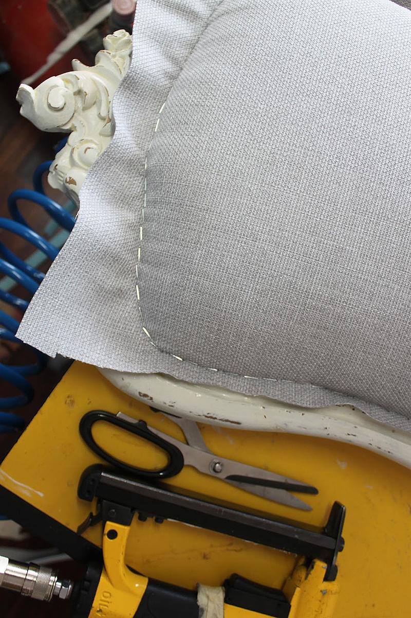 La tapicería elegida es una tela de saco en tonos grises. El galón gris oscuro le da un poco de contraste con el blanco