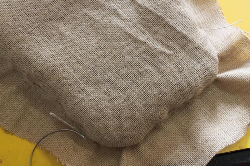 La coca rellena de crin constituye la forma del asiento y respaldo. Es bonito conservar las formas originales del mueble, así que usando un cordón de palomar y una aguja curva de tapicero se frunce la arpillera y se le da forma